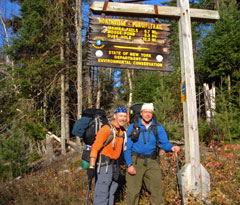 Two hikers stand beneath the trail sign at one end of the Northville-Placid trail.