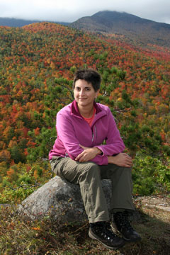 A woman in a pink sweater sits on a rock with mountain hillsides with fall foliage in the background