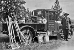 A 1925 photo of a forest ranger standing by his truck and firefighting tools