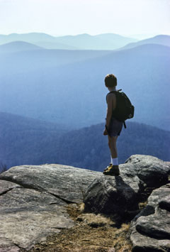 A boy stands on a rocky summit, looking out over mountain ranges