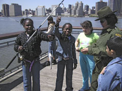 Two young girls fishing in New York City, hold up a fish they caught.