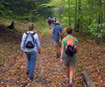 A group of people hiking on a trail in early fall