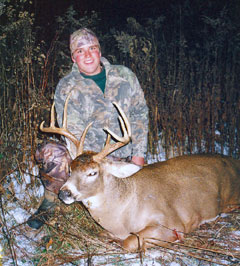 A young man sits behind a deer he killed