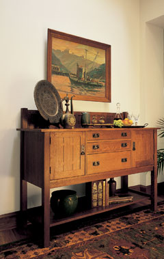 A wooden sideboard with a painting above in a room