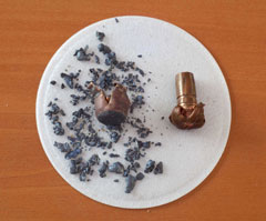 A white plate with lead ammunition fragments and a copper bullet that has been fired