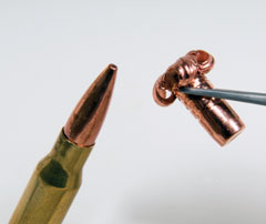 A copper bullet and the resulting mushroom form of a bullet that has been fired