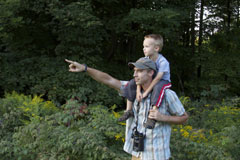 A father with binoculars, stands in a field with his son on his shoulders