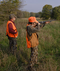 A youth hunter aims a rifle while an adult hunter looks on
