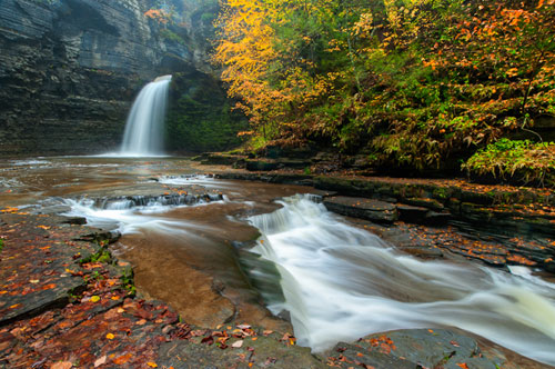 A waterfall and water flowing in a shallow rocky creek surrounded by trees with fall color