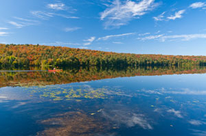 Blue sky and fall foliage reflected in a still lake