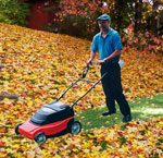 A man mowing through a thick layer of fall leaves on a lawn