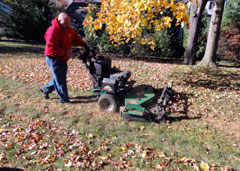 A man mows over fallen leaves with a lawn mower