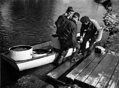 Three men at the end of a wooden pier,carrying large buckets containing fish for stocking from a boat