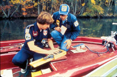 Two biologists in a boat measuring a fish