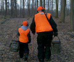 A grandpa and grandson wearing hunter orange, heading out to hunt