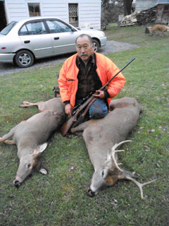 A man kneels on the grass between two dead deer holding a gun