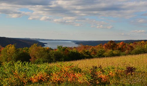 View of a long lake in the distance with fall foliage in the foreground
