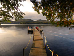 A view down a dock over an Adirondack lake with mountains in the distance