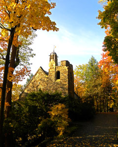 A stone chapel surrounded by trees with fall color