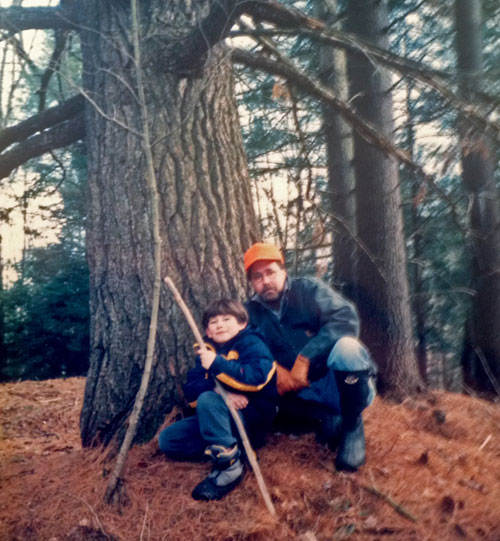 A man and his son sit at the base of a large pine tree.