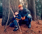 A father and son sit at the base of a large pine tree