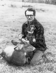 A man holding a wirehaired dachshund kneels by a dead deer