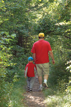 A man and boy in red shirts walk a path in the woods