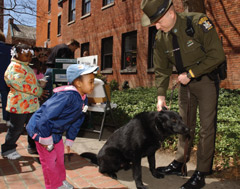 Children say hello to an ECO and his K-9 unit dog