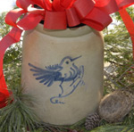 A bird decorates a stoneware crock with a red bow on top