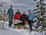 Four winter campers and their dog in the snow on Mount Blue
