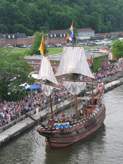 A replica of the ship half Moon sails by hundreds of onlookers
