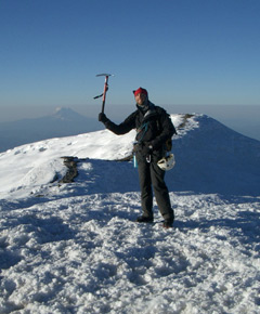 A man with an ice pick standing on a snowy mountain peak
