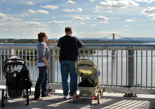 A man and a woman with strollers at the railing of a pedestrian bridge looking at the view