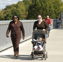 Two women, one with a baby in a stroller, on the walkway