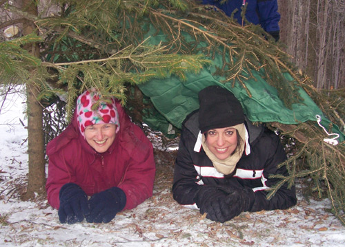 Two women in a makeshift shelter of evergreen branches