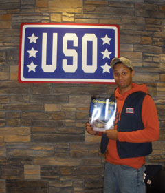 A member of the USO holds up a copy of Conservationist magazine