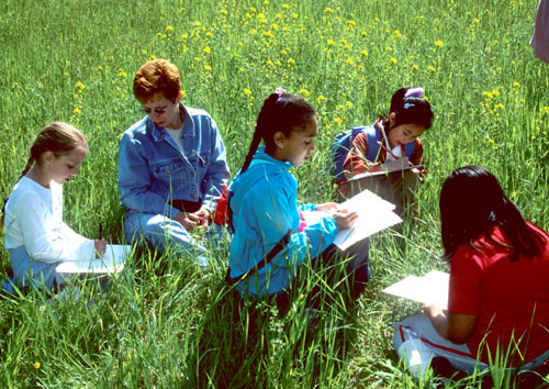 A group of children taking notes in a field