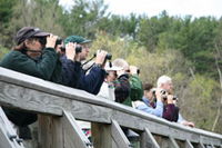 A group of adults leans on a railing and looks through binoculars