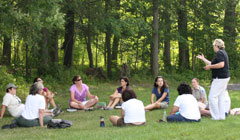 A group of teachers sitting on the grass listening to a workshop leader