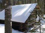 A snow-covered lean-to in a forest setting