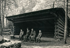 A black and white historic image of a family sitting on the front edge of a lean-to