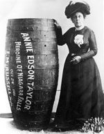 A black and white image of Annie Taylor in a long dress standing next to the barrel she went over Niagara falls in