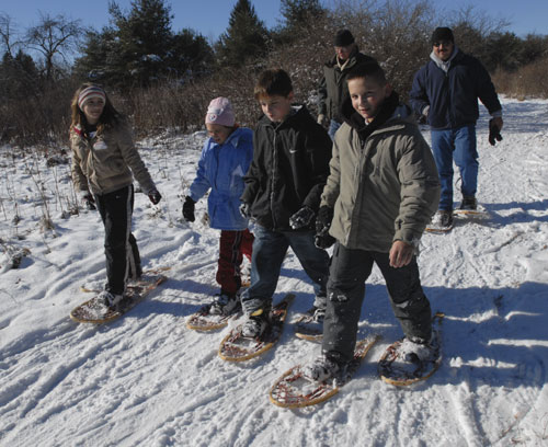 A group of kids and two adults snowshoeing on a sunny day