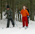 Three kids cross-country skiing on a trail in the woods.