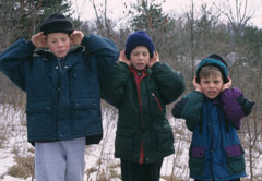 Three boys with their hands cupped by their ears listening for wildlife