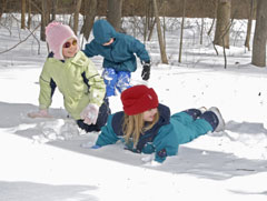 Three young girls playing outdoors in the snow