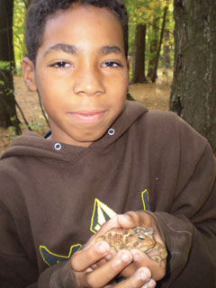 A young black boy in a brown sweatshirt holding a frog