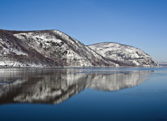 Snow covered hills reflected in the Hudson River at Storm King