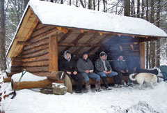 Four men and a dog inside an Adirondack lean-to in winter