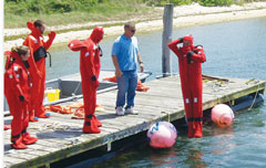 Crew in red immersion suits practice using them off a dock